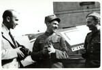 Julien Bryan and two Polish soldiers chat in front of a downed German airplane.