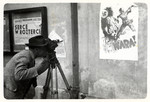 Julien Bryan films an anti-Nazi propaganda poster affixed to a wall in besieged Warsaw.