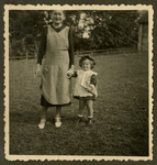 Rosian Bagriansky stands outside holding hands [with her nanny].