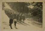 SS officers and enlisted men march to shooting practice.
