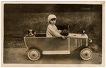 Portrait of Sonia Pressman driving a toy car, in Germany, early 1930s.