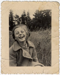 Close-up portrait of a laughing Jewish girl, Rosian Bagriansky  in hiding on the farm of her rescuer Lyda Goluboviene, in Kulautova, Lithuania.