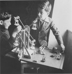 Wolfgang Schaechter (right) and Marcel Brettler (left) play with a mechanical erector set in the Enns displaced persons camp.