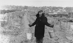 A Jew wearing a yoke across his shoulders carries two pails of water to an agricultural plot in the Kovno ghetto.