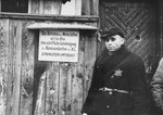 A Jewish man standing at an entrance to a workshop in the ghetto.