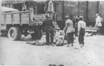 Under the supervision of Romanian guards, Gypsies load the corpses of victims of the Iasi-Calarasi death onto trucks in Targu-Frumos.