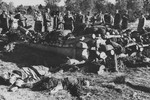 Soviet investigators in the Klooga concentration camp examine corpses stacked for burning.