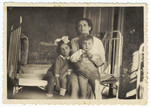 Portrait of a Romanian Jewish mother and her two children sitting on a bed.