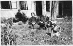 Four young Jewish girls play in the garden while their grandfather looks on.