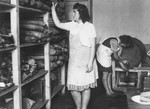 Ethel Zloczower, a Romanian Jewish teacher, stands by a bread pantry in the children's home in Vence.