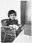 A young Jewish girl listens to a radio with head phones.