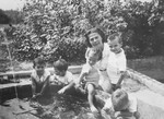 Lydia Turznikova helps a group of toddlers playing in a fountain, in the MACE children's home in Vence.
