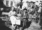 Mr. and Mrs. Nadal, Spanish refugees and staff of Chateau de la Hille, relax outside by knitting and reading.