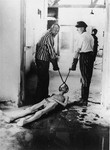 Survivors of the Dachau concentration camp demonstrate the operation of the crematorium by dragging a corpse towards one of the ovens.