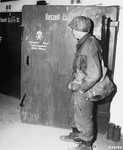 A soldier from the U.S. 7th Army examines the door to a gas chamber in the Dachau concentration camp.