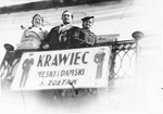 Henia Zoltak (left) and two friends stand on the balcony of her home above a sign advertising the family store.