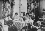 Four young girls from Germany, including Anne and Margot Frank, have a tea party with their dolls at the home of Gabrielle Kahn in Amsterdam.