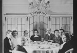 Jewish friends who have met for tea, including the parents of Anne Frank, pose around a table in a private home in Mannheim, Germany, shortly before many of them fled the country as refugees of the Nazi regime.