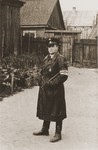 Orenstam, a member of the Jewish ghetto police, stands outside a house in the ghetto.