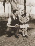 A Jewish DP child poses outside with a young man in the Cremona displaced persons camp.
