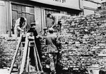 Polish and Jewish laborers construct a section of the wall that separated the Warsaw ghetto from the rest of the city.