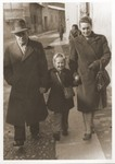 A Jewish DP family walks along a street in Cremona.