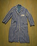The striped overcoat of a prison uniform worn at the Buchenwald concentration camp bearing a purple triangle on the number patch.