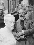 Sculptor Naum Aronson poses next to his sculpture of Louis Pasteur.