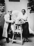 Sculptors Naum Aronson and Miriam Berlin pose on either side of a stool in Aronson's studio in Paris.