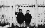 Agnes and Zsuzsi Laszlo stand together next to a wooden fence in their small farming community of Pogony Puszta.