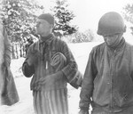 Tahae Sugita (right), a Japanese-American soldier with the 522nd Field Artillery battalion, stands next to a concentration camp survivor he has just liberated on a death march from Dachau.