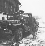 A Japanese-American soldier poses next to his jeep in the town of Waakirchen, where the 522nd Field Artillery Battalion set up a temporary field hospital for survivors of a Dachau death march.