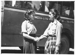 Two teenage girls shake hands in front of a bus outside the Selvino children's home.