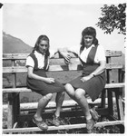 Two teenage girls sit on a wooden bench on the grounds outside the Selvino children's home.