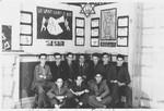 Members of the Revisionist Zionist youth group in Shanghai pose in front of a wall of posters and photographs.