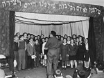 Moshe Zeiri conducts a children's choir during a performance at the Youth Aliyah children's home in Selvino, Italy.