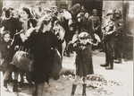 Jews captured by SS and SD troops during the suppression of the Warsaw ghetto uprising are forced to leave their shelter and march to the Umschlagplatz for deportation.