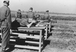 Karl Hoecker shoots his rifle while lying on a wooden table during target practice.