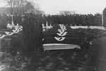 German troops stand at attention alongside a row of coffins during a military funeral near Auschwitz.