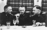 Three SS officers gather for drinks in a hunting lodge.
