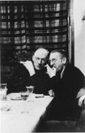 Two Germans converse at a table at a hunting lodge.