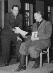 An American military lawyer presents a document to defendant Johann Kick during the Dachau war crimes trial.