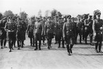 Nazi officers walk towards the dedication of the new SS hospital in Auschwitz.