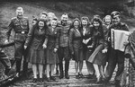 Nazi officers and female auxiliaries (Helferinnen) pose on a wooden bridge in Solahuette.