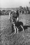 "SS officer Karl Hoecker pets his dog.  The original caption reads ""Mein Schaeferhund ,Favorit'"" [My Shephard dog ,Favorit']."