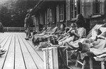 SS officers together with women and a baby relax on lounge chairs on a deck in Solahuette.