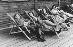 SS officer Karl Hoecker relaxes with women in lounge chairs on the deck of the retreat in Solahuette.