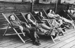 SS officer Karl Hoecker and some women relax on lounge chairs on a deck in Solahuette.