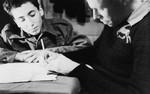 Two teenage boys write in a notebook in a boarding school in Switzerland.