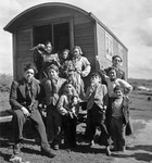 Roma (Gypsy) children and youth pose around the entrance to a caravan.
